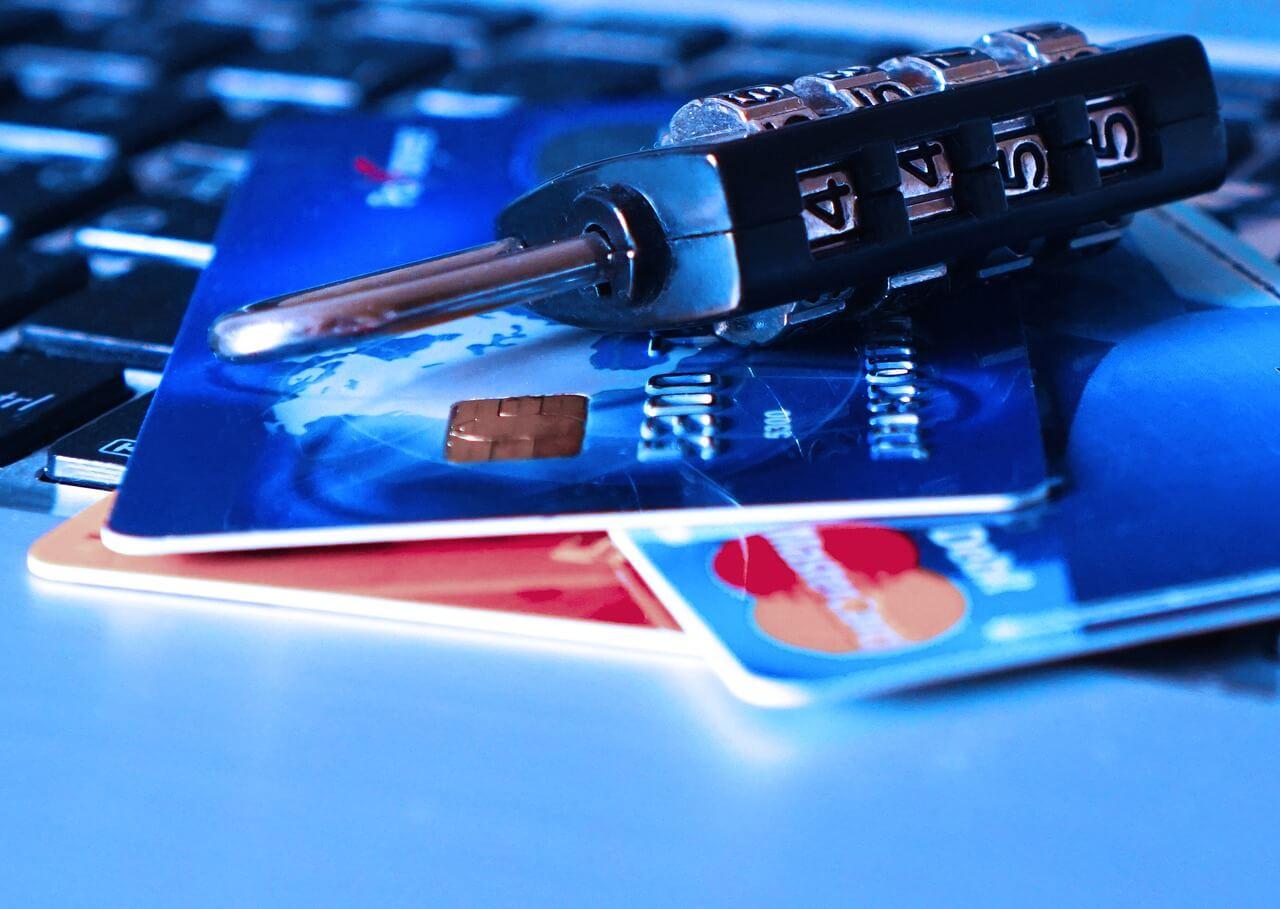 carte di credito su scrivania con sopra un lucchetto e dietro tastiera