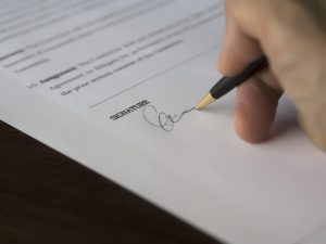 mano che firma un foglio con la penna