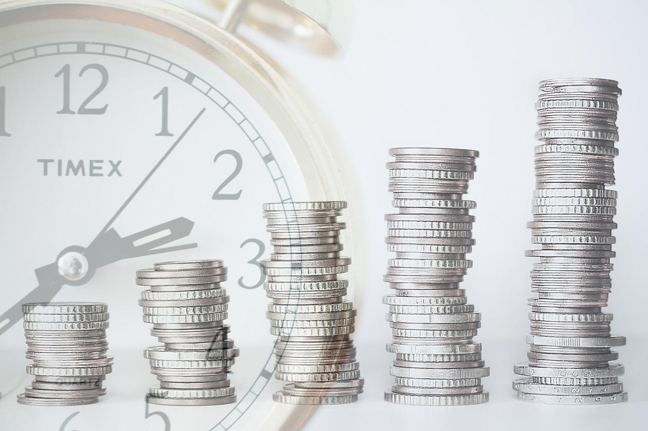 pile di monete con orologio sullo sfondo