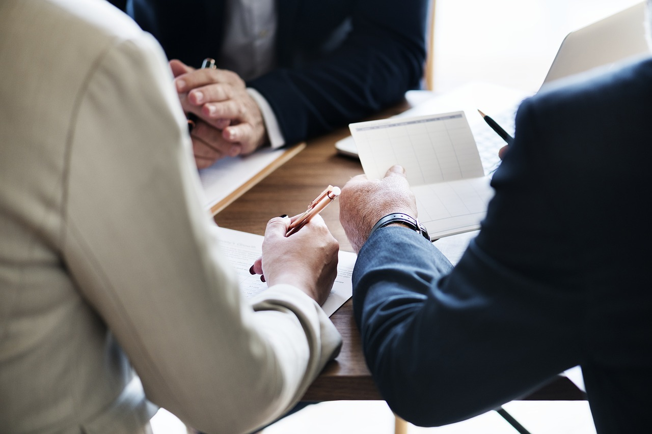 persone con penna in mano che stanno per firmare dei fogli